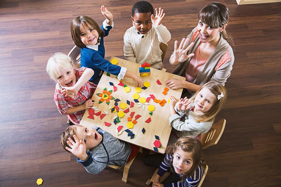 children sitting at table waving at camera
