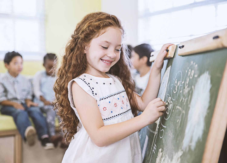 girl writing on black board